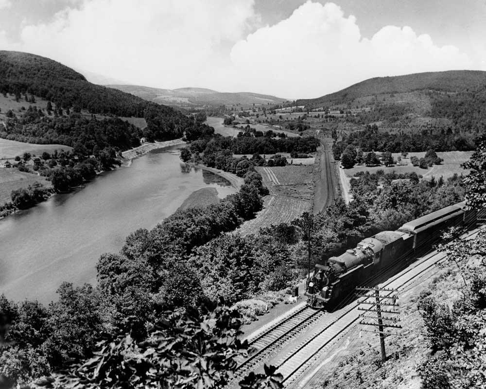Steam locomotive with passenger train on hillside above river valley