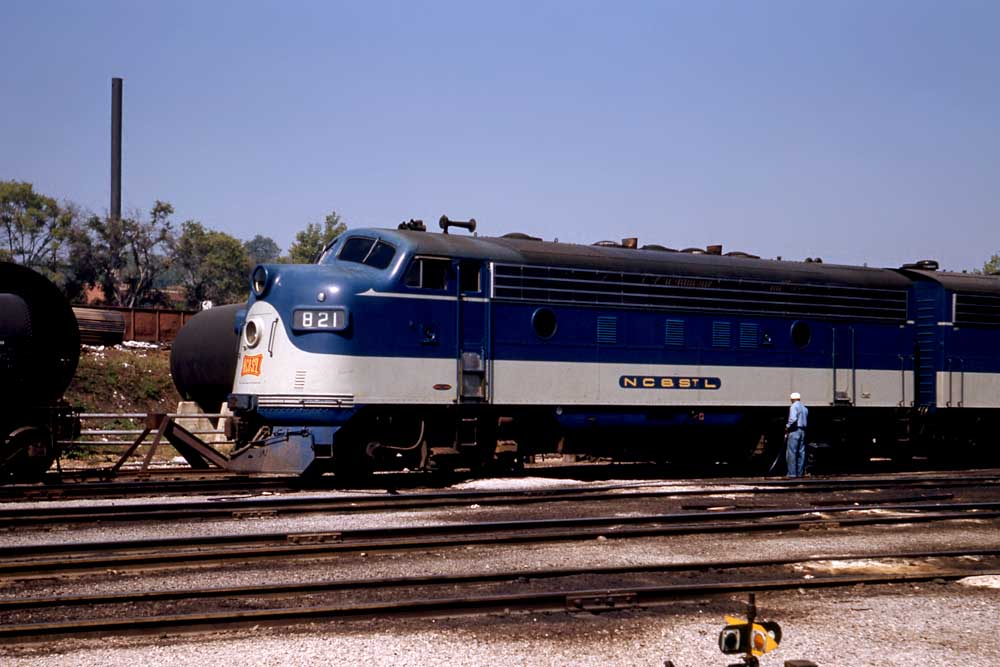 Man in coveralls stands by blue and gray streamlined diesel locomotive in profile