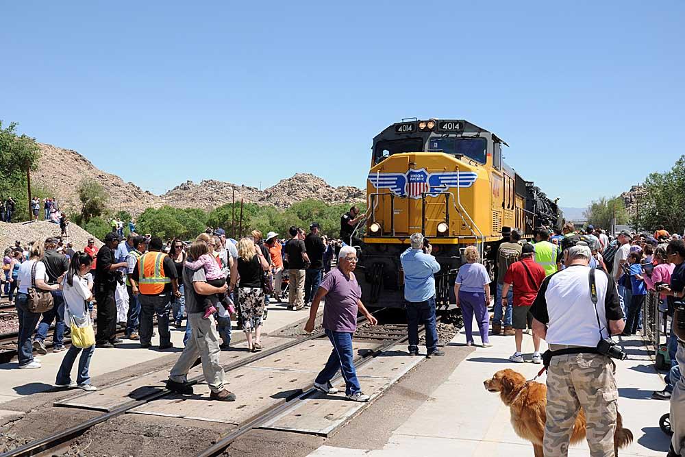People walk on crossing in front of yellow diesel locomotive