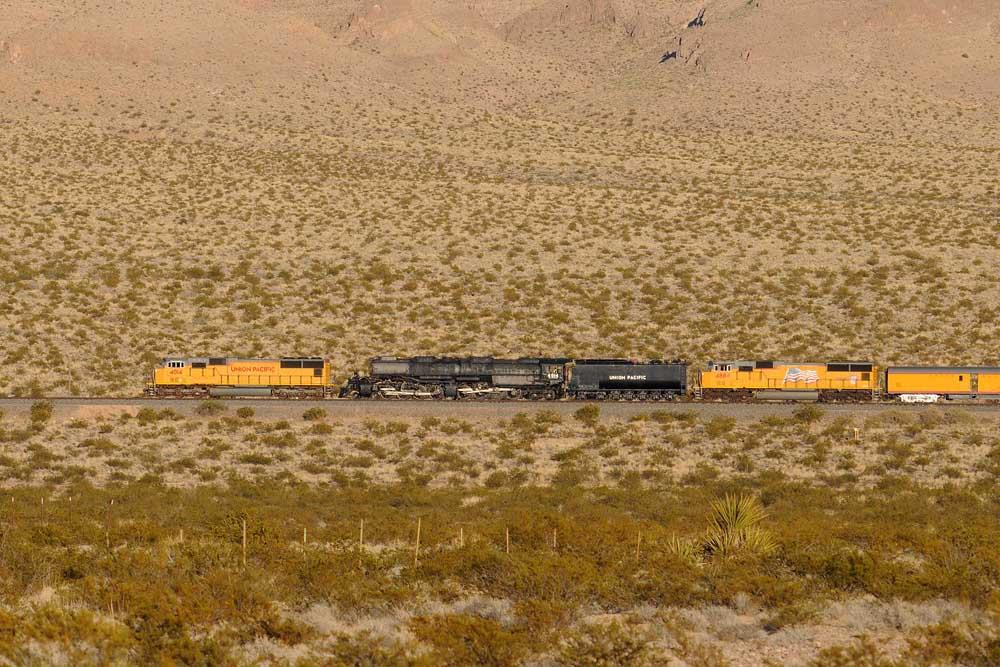 Train in profile against hillside in low evening light