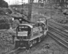 Black-and-white photo of road-switcher diesel locomotives leading freight train from multi-track main line to single-track branch line
