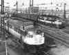 High-angle view of streamlined diesel and electric locomotives on parallel tracks.