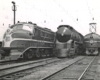 Black-and-white three-quarter-angle photo of three locomotives lined up on adjacent tracks