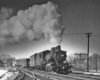Black-and-white photo of steam locomotive with short freight train.