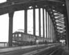 Black-and-white photo of people watching electric locomotives on bridge with freight train