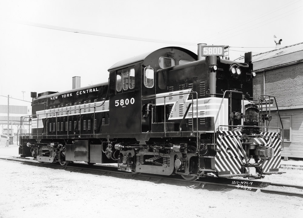 Three quarter angle black and white photo of a diesel locomotive switching route.