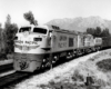 Three-quarter-angle black-and-white photo of Union Pacific two-unit gas-turbine electric locomotive on freight train.