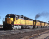Three-quarter-angle color photo of four Union Pacific road-switcher diesel locomotives on freight train.
