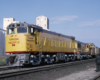 Three-quarter-angle color photo of two Union Pacific road-switcher diesel locomotives on freight train.