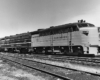 Black-and-white three-quarter-angle photo of three-unit streamlined diesel locomotive.