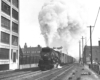 Black-and-white photo of steam locomotive with long train of boxcars