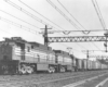 Black-and-white photo of two road-switcher electric locomotive with freight train
