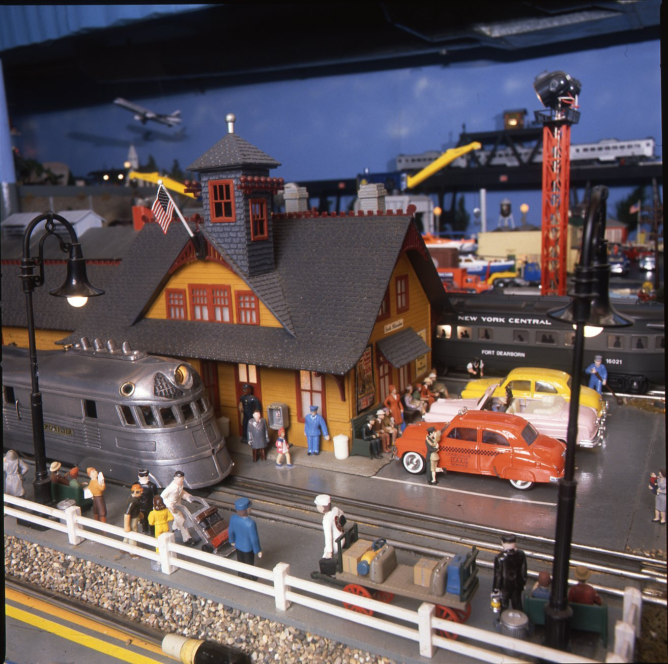 A busy station scene on an O gauge layout.