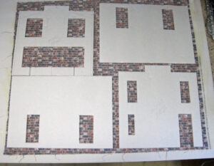 Side panels of a model structure laid out on top of fabric