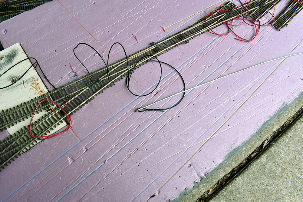 Ladder tracks on pink extruded-foam insulation board with wires attached. Black wire twisted onto baling wire push rod