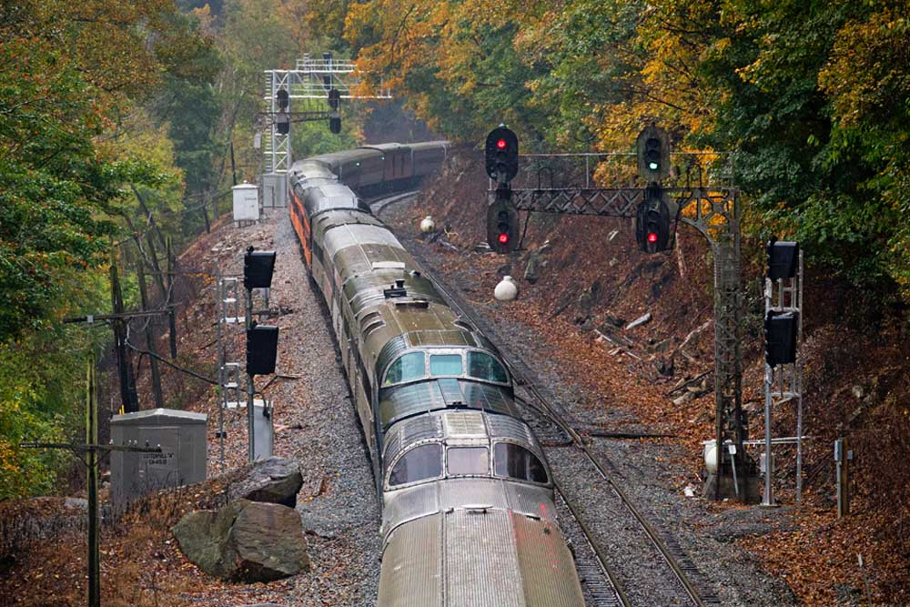 Passenger train dome cars pass signals among colorful trees