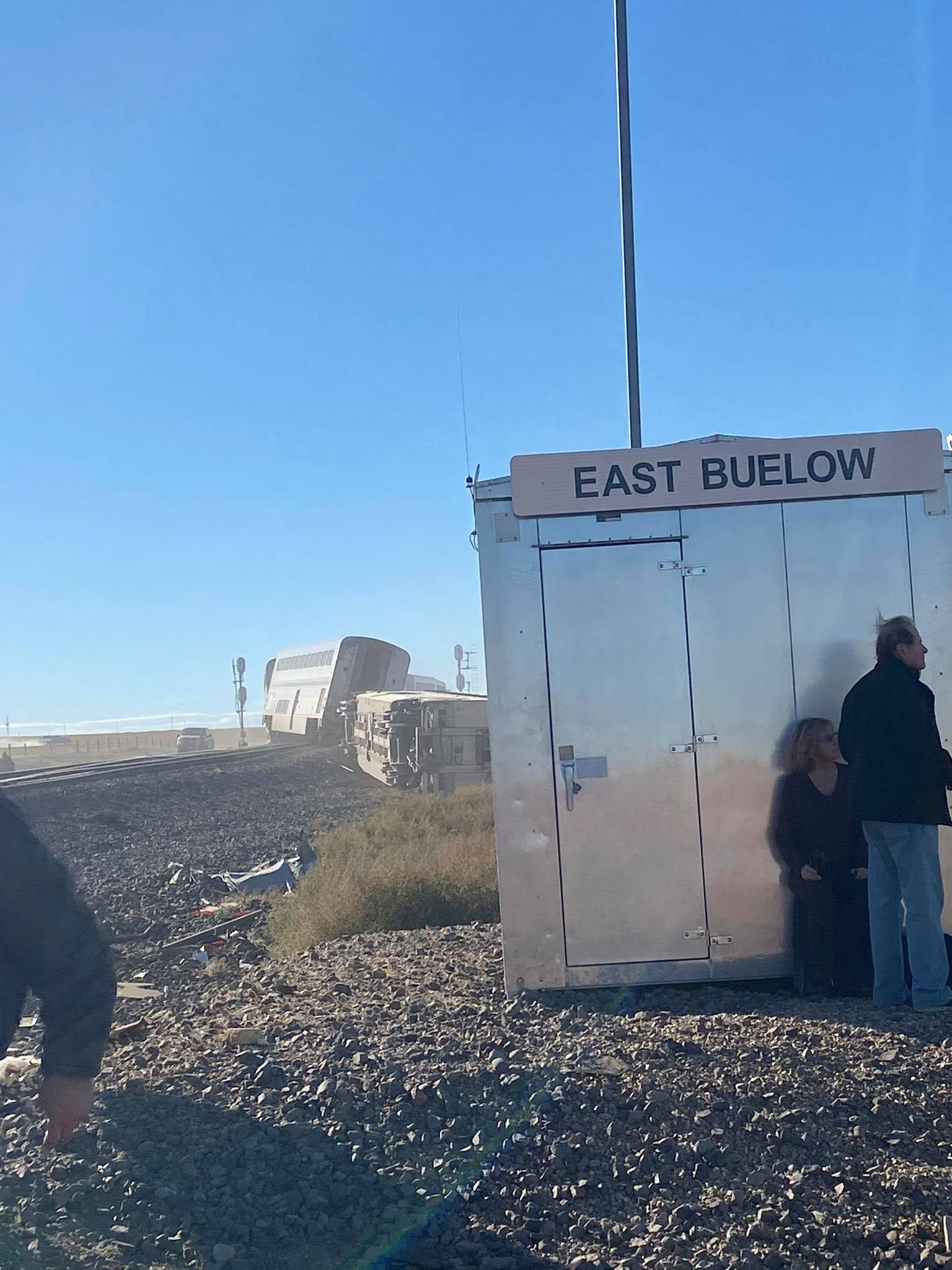 People stand by silver box near derailed train cars