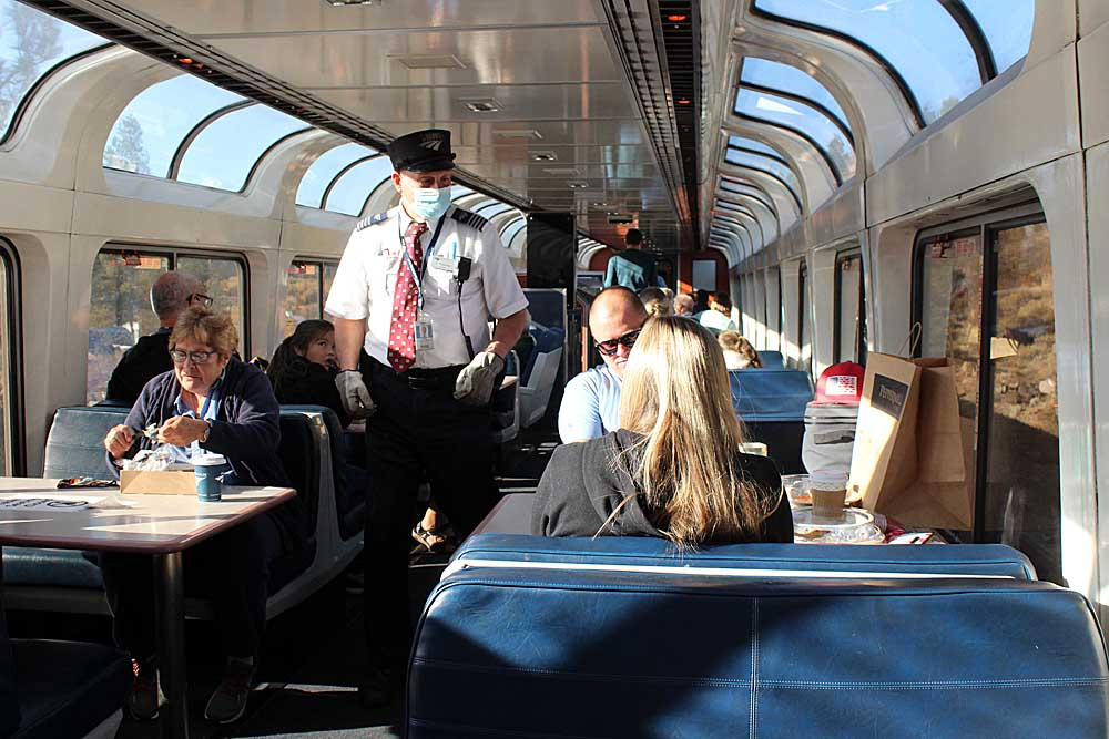 People in glass-covered passenger rail car
