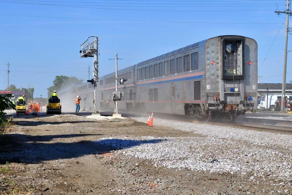 Bilevel passenger train rolls through grade crossing under construction