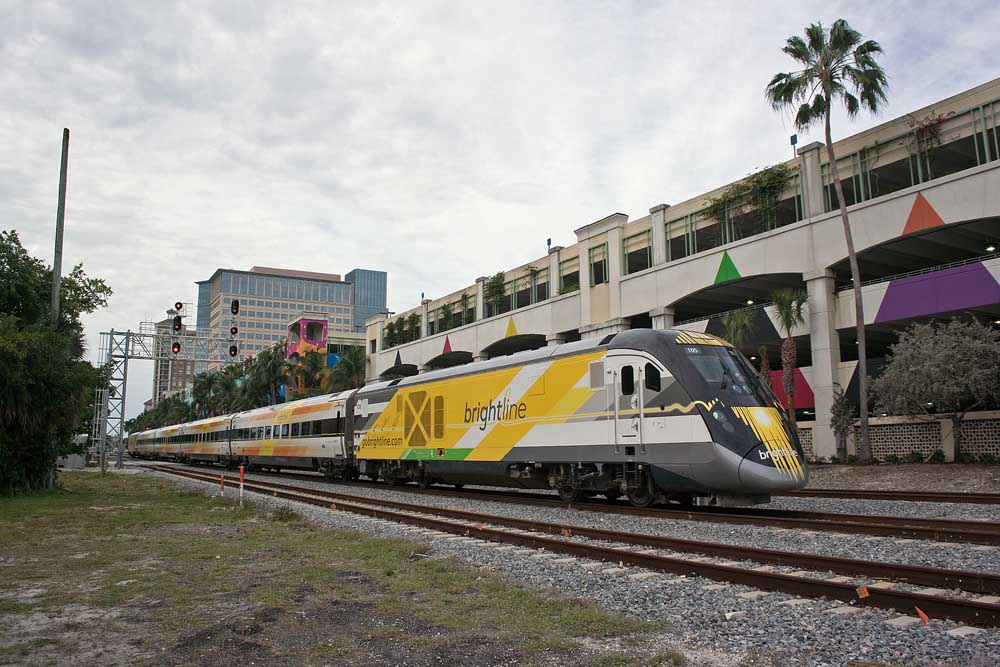 Multi-colored streamlined passenger train passes colorful parking garage and palm trees.