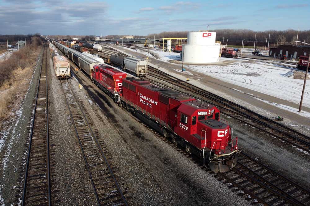 Red diesel locomotives with cars in yard
