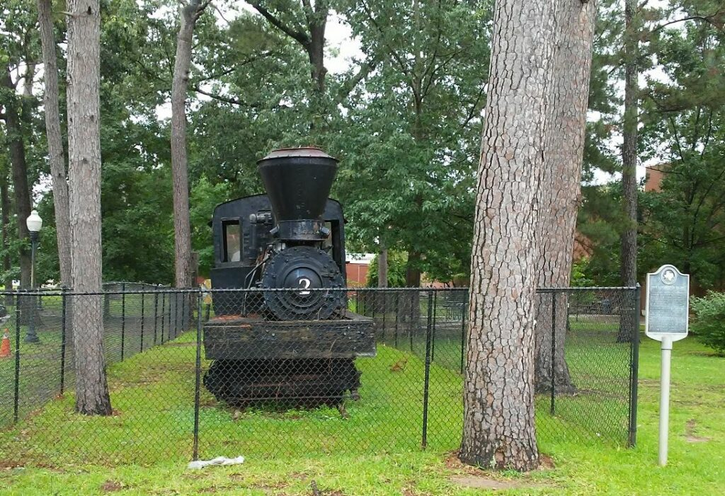 Steam locomotive displayed behind fence among trees