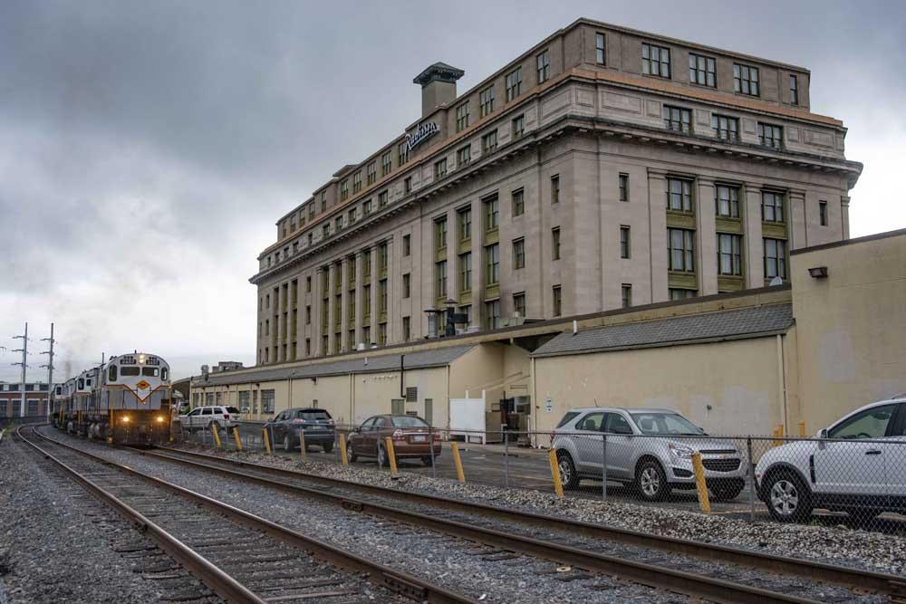 White diesel locomotive passes stone station on overcast day
