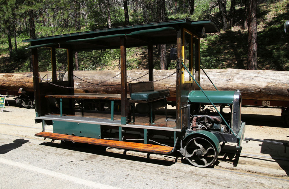 Antique car with open sides, fitted with flanged wheels, to move on rails and carry passengers.