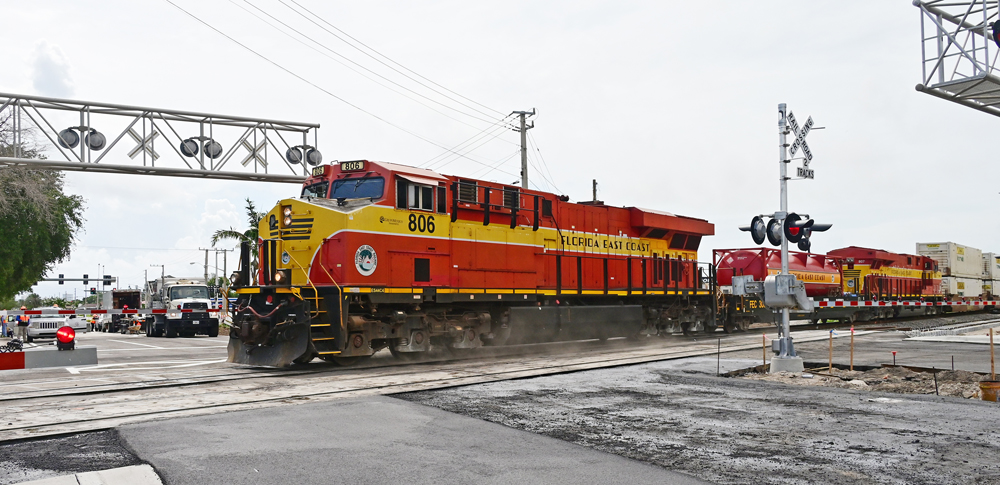 Red-and-yellow locomotives with fuel tender cross street