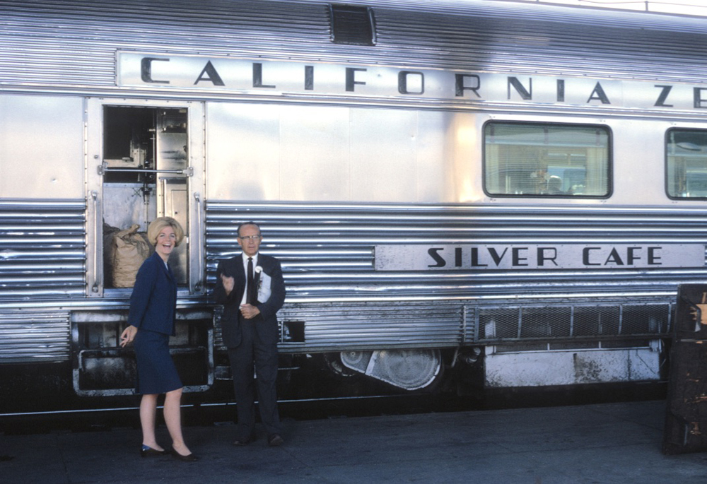 Blonde woman in dress and man in suit standing next to passenger car on station platform.