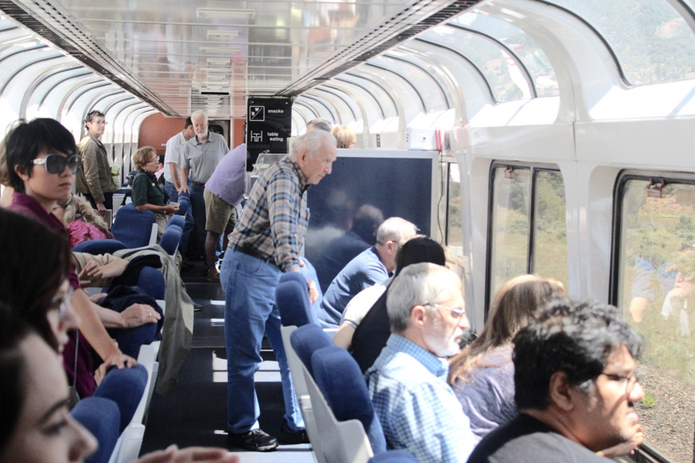 People standing and sitting, facing out windows of passenger car