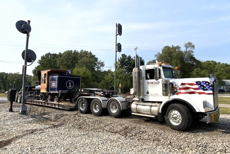Small steam locomotive on truck with flatbed trailer