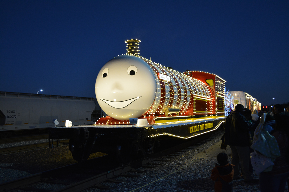 Flatcar decorated to look like steam locomotive, covered with holiday lights