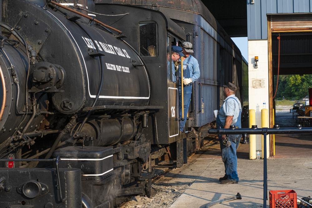 Crew members talk at cab of steam locomotive