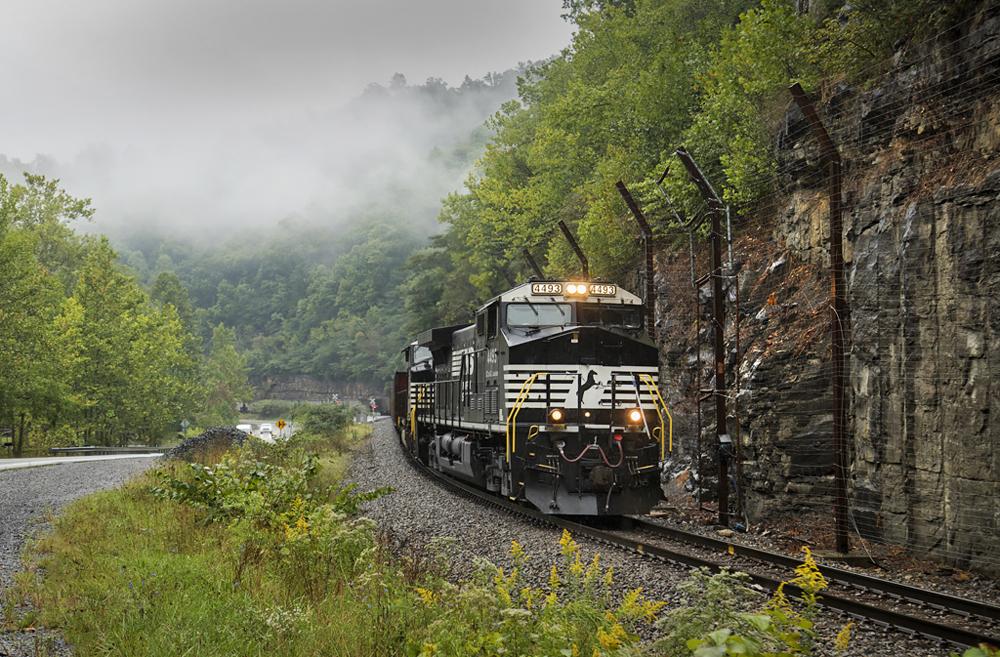 Black locomotives lead train around curve in mountains