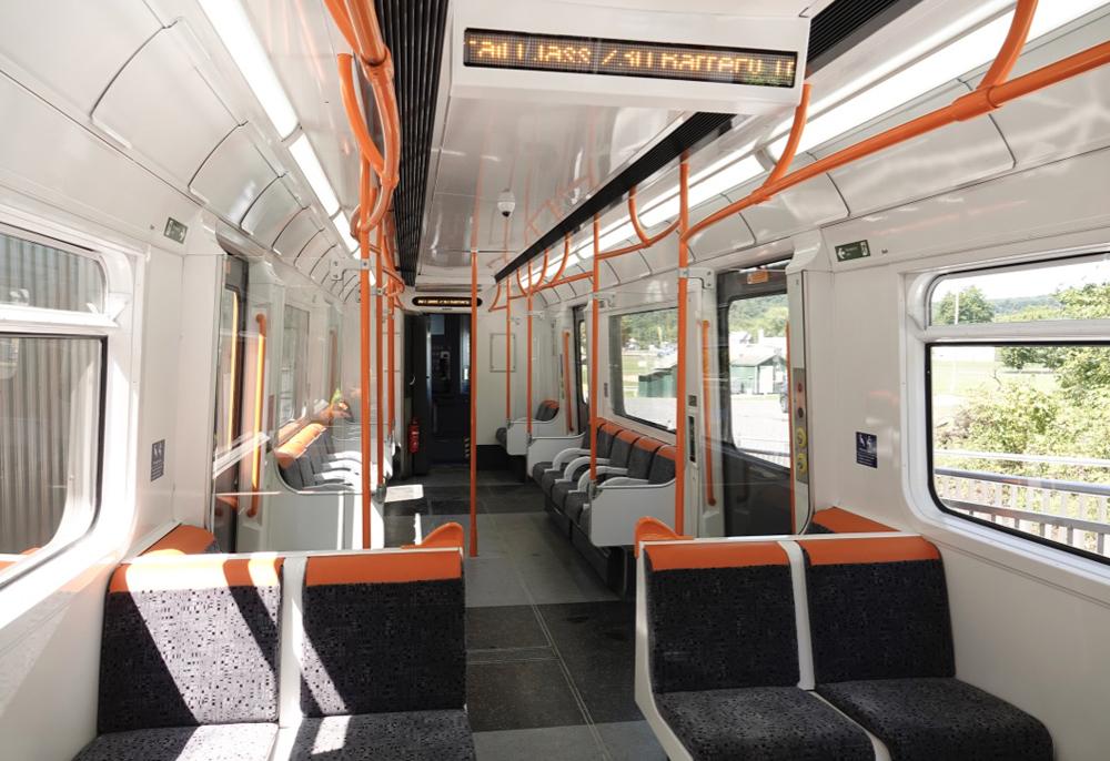White passenger car interior with black seats and orange trim