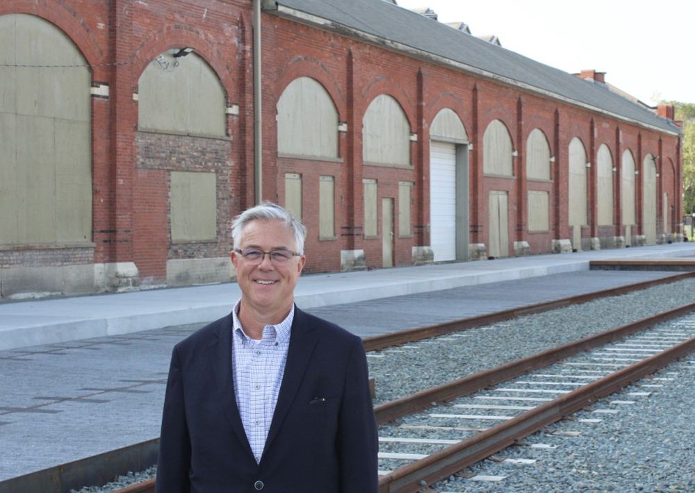 Man in blue sportcoat stands in front of brick factory building