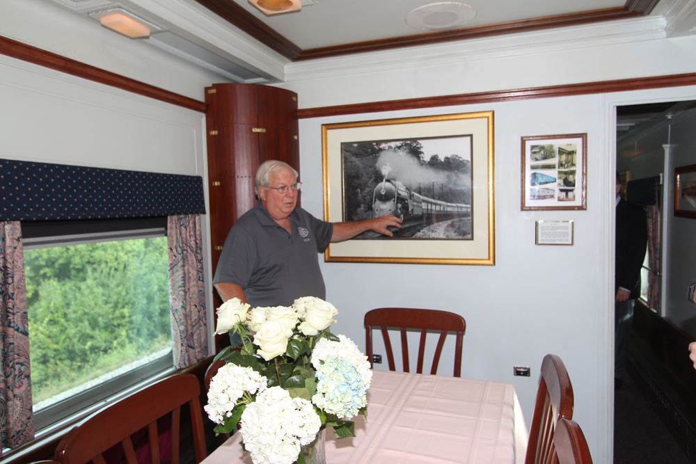 Man gesturing to framed photo inside private car