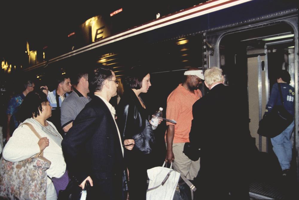 Crowd of people boarding passenger car