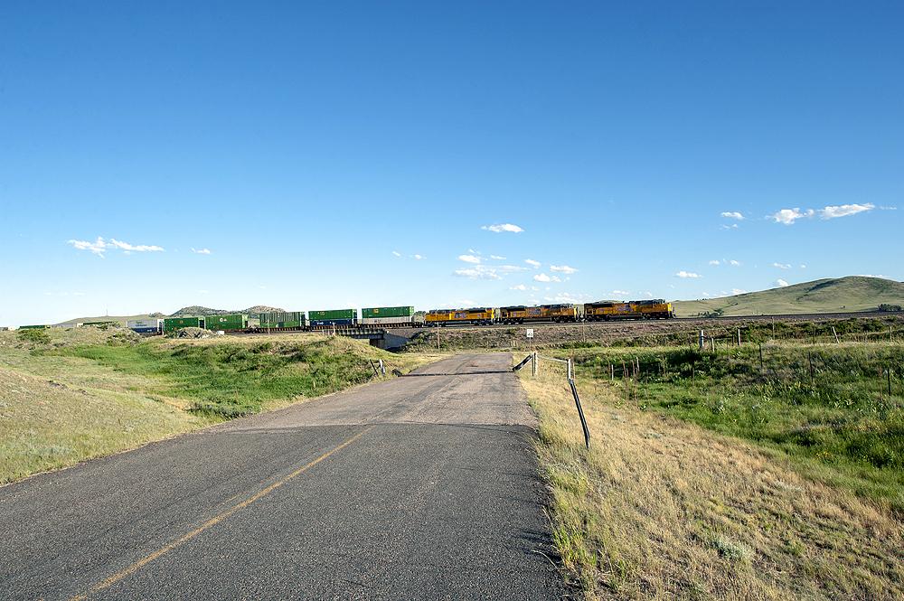 Three yellow Union Pacific locomotives lead an intermodal train uphill amid rolling hills and grassland.