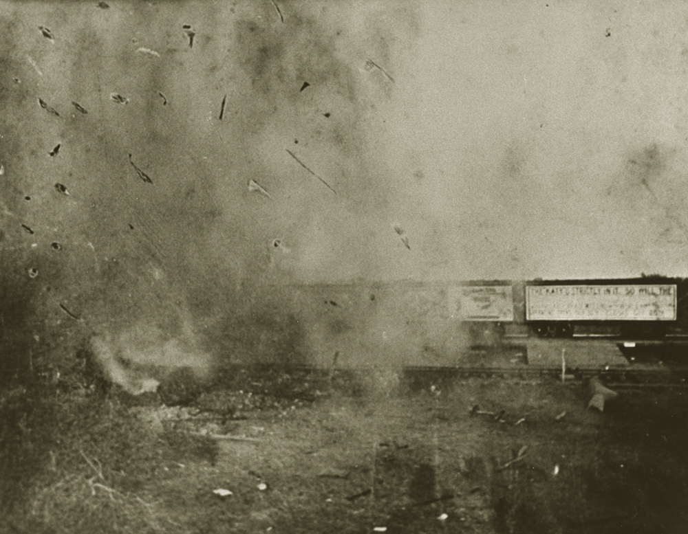 A cloud of smoke and debris with railroad cars visible to one side.