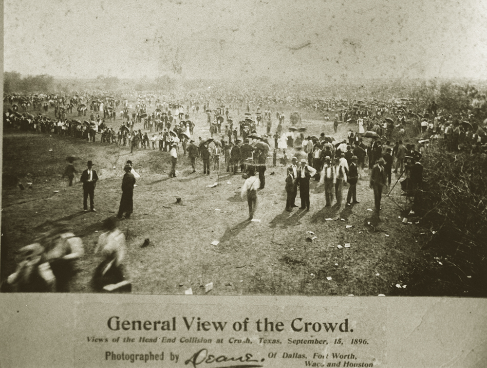 Large crowd of people, mostly men in suits and hats, in open field.