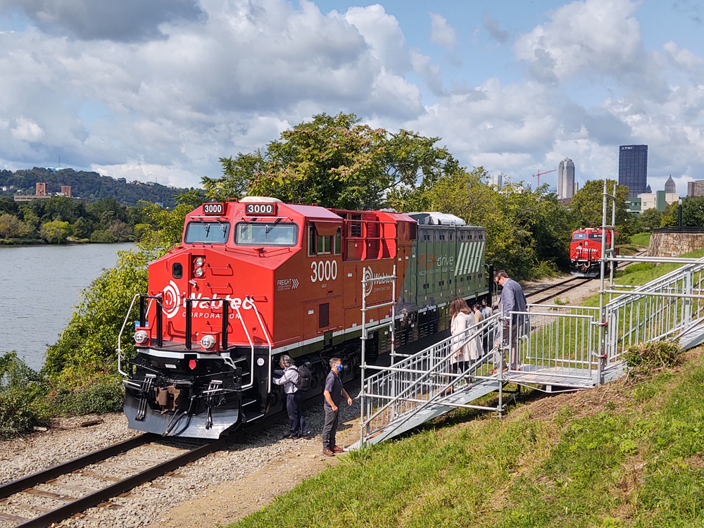 Red and gray locomotive parked on track along river
