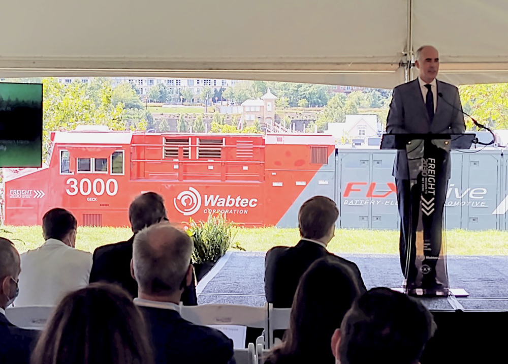 Man speaking at podium with locomotive in background