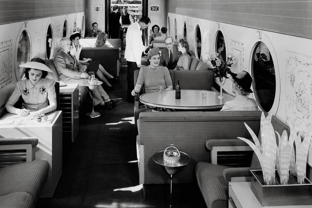 People seated in railroad lounge car with porthole windows