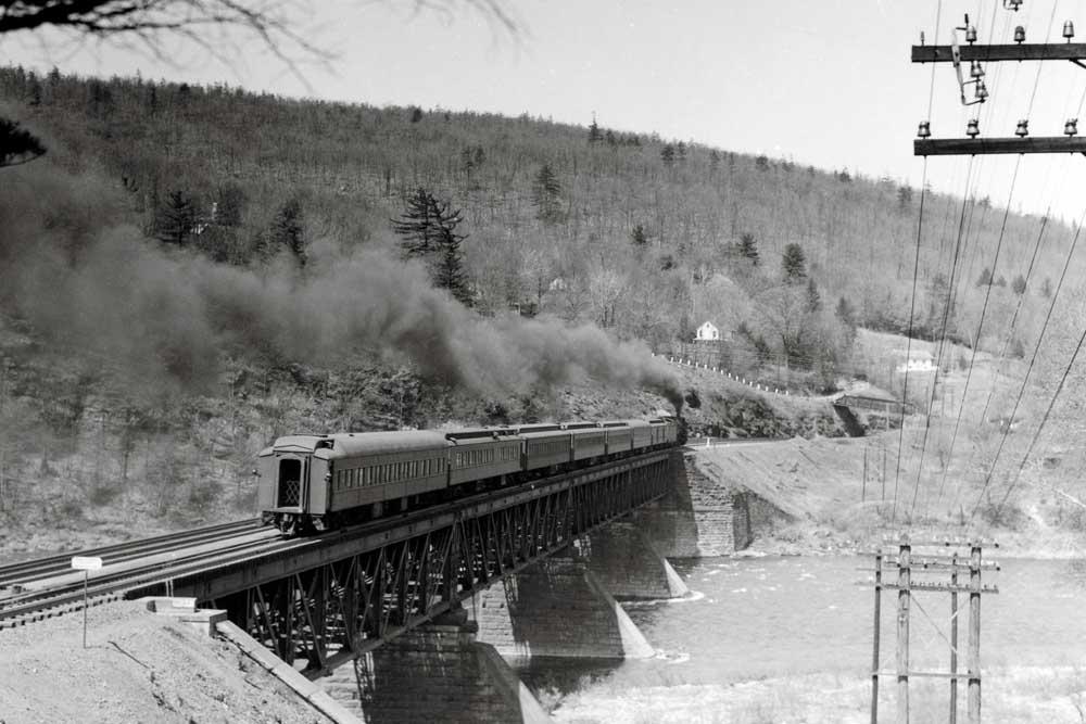 Rear of heavyweight passenger train on bridge
