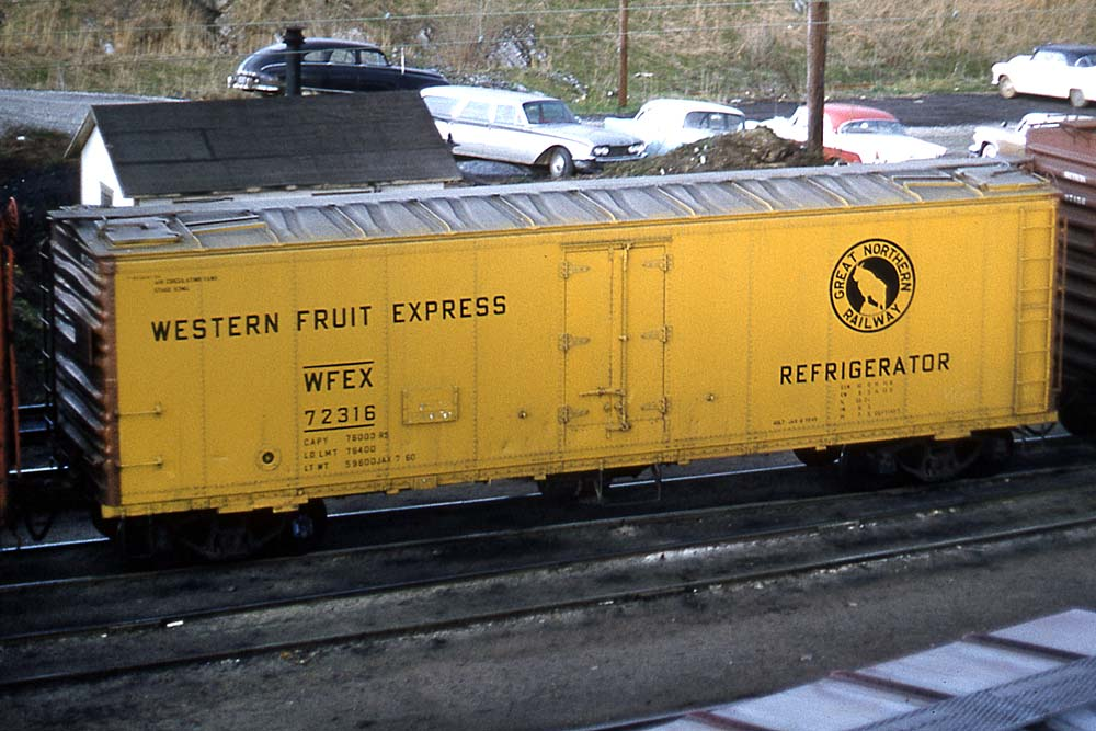 Yellow ice-cooled refrigerator car with silver roof and brown ends