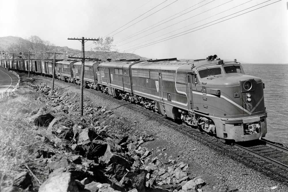 Streamlined passenger diesels haul freight cars along a waterfront