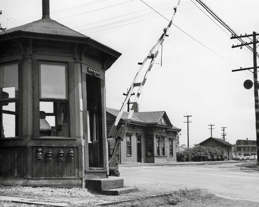 Octagonal watchman shanty and wooden crossing gates in front of wooden station