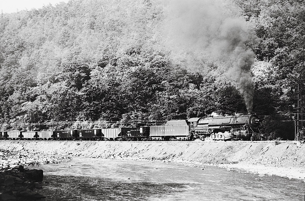 Black-and-white broadside photo of 2-10-2 steam locomotive with hopper cars beside a river